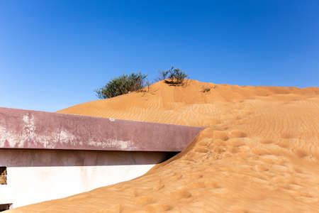 Old residential building buried in sand dune on a desert in Al Madam ghost village in Sharjah, United Arab Emirates.