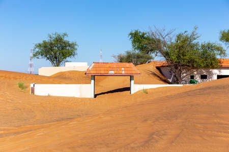 White entry gate buried in sand in Al Madam ghost village, with sand dunes and wild ghaf trees.