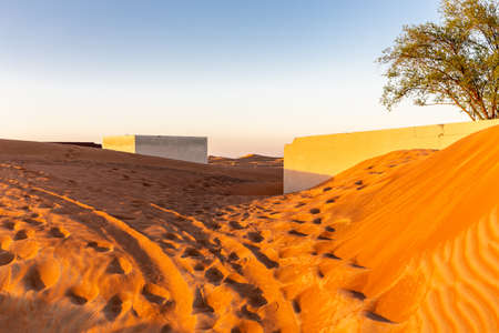 Al Madam ghost town buildings buried in sand dunes in the desert, United Arab Emirates, sunset.