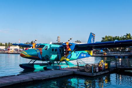 Male, Maldives, 20/11/2020. Trans Maldivian Airways colorful seaplane Twin Otter Series 400 docked at seaplane terminal, Four Seasons Resort painting. Sajtókép