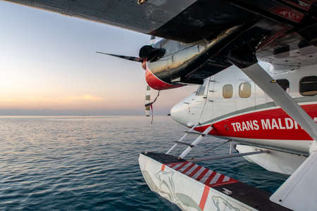 Maldives, 20/11/2020. Trans Maldivian Airways seaplane Twin Otter Series 400 floating on the ocean surface with sunset in the background.