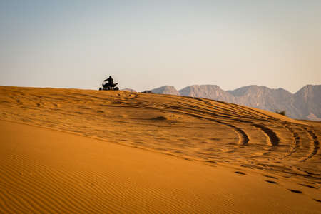 Silhouette of a quad driving up the sand dune in the desert, with tire tracks behind and mountains in the background, sunset, Fossil Rock, Sharjah, United Arab Emirates.