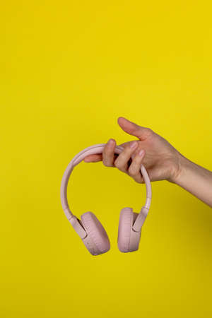 A young woman holds a pair of pink wireless headphones in her hand. Hand of a girl with headphones on a yellow background. Musical concept.
