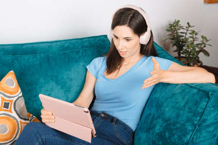 Close up view portrait young attractive millennial woman sits on couch in headphones in living room having unpleasant video call conversation using digital tablet. Brunette girl has spirited debate