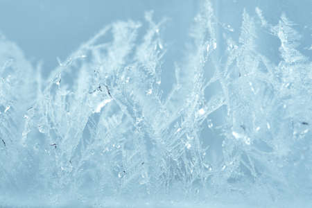 Closeup winter window pane coated shiny icy frosted patterns. Abstract beautiful ice flowers pattern, macro view background. Snowflakes on winter glass, natural texture. New year Christmas backdrop.