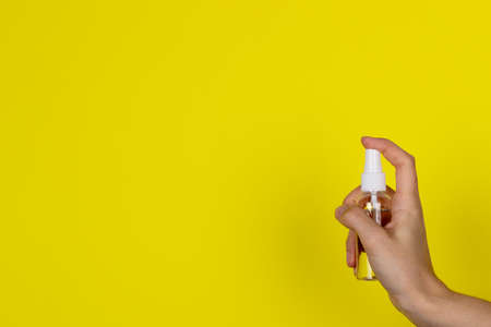 A young woman holds an antiseptic in her hand. Transparent bottle of sanitizer on a yellow background in the female hand. Copy space for text or design.Health care concept Reklamní fotografie