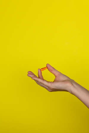 The drug in the girl's hand. A young woman holds an orange medicine capsule in her hand. Copy space for text or design. Vitamin on a yellow background. Health care concept.