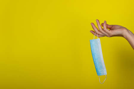 A young woman holds a medical face mask in her hand. Protective mask on a yellow background in the girls hand. Copy space for text or design. Health care and medical concept