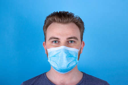 Calm European man in a medical face mask on a blue background. Composed, peaceful and smiling man in a protective mask. A person wears a face mask to protect himselve and others from the virus