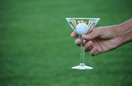 copa martini: pelota de golf y tees en vaso de martini con copyspace