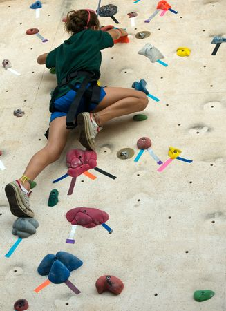 belay: Teen taking a BIG step up an artificial wall