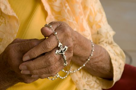 elderly caucasian hands holding a silver rosary photo