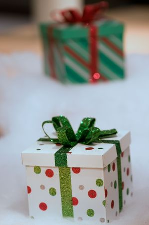 two gifts wrapped in red and green on a white snow background with narrow DOF Stock Photo - 5927428