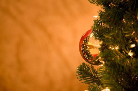 gold reflective ornament ball on a Christmas tree with gold background for copy space Stock Photo - 5927431