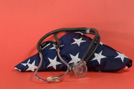 stethoscope on folded US flag with red background Stock Photo - 6331308