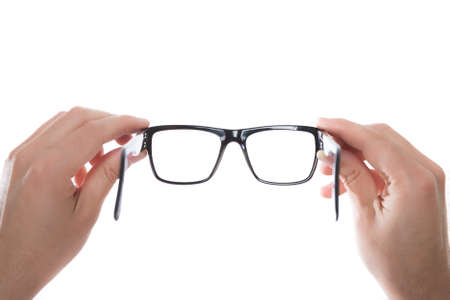 Hände, die schwarze Brille auf weißem Hintergrund