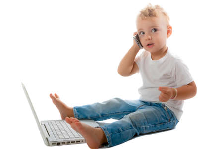 child sitting on the floor with phone and laptop photo