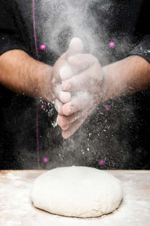 sprinkling flour with hands on bread dough Stock Photo