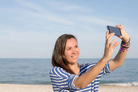 smiling young woman taking a selfie with a smartphone on the beach photo