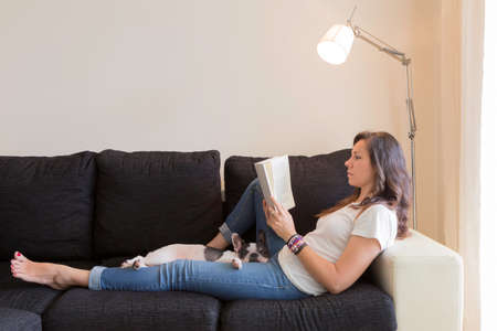 young woman lying on a sofa reading a book with a cute white and black french bulldog  Stock Photo