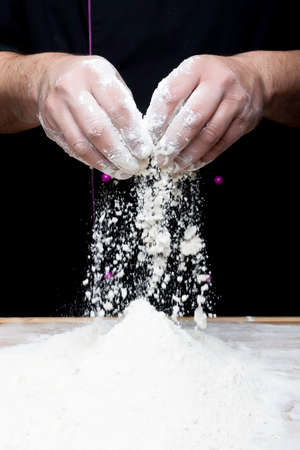 the chef hands are dropping flour over a wooden table
