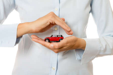 hands of a business woman holding a red toy car isolated on a white background