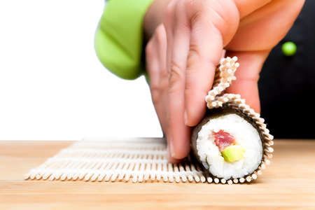 closeup of chef hands rolling up sushi - focus on the roll Stock Photo