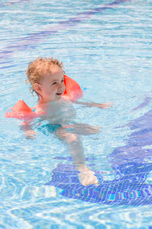 cute child with floats enjoying in the swimming pool - focus on the face photo