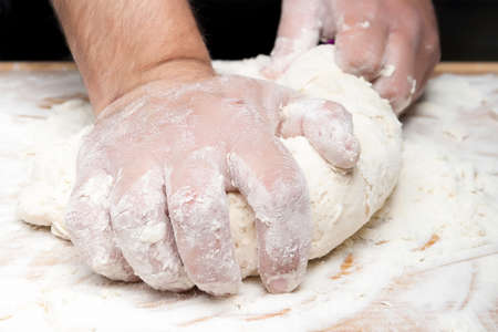 closeup of hands kneading bread on a wooden board - focus on the index finger