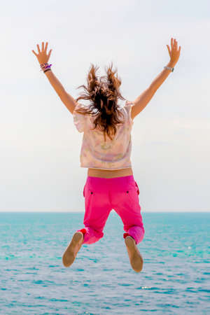 euphoria: back of a young woman jumping up with euphoria in the air by the sea - focus on the girl Stock Photo