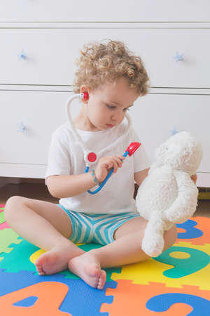 sitting child playing to be a doctor with a toy stethoscope and a teddy bear photo