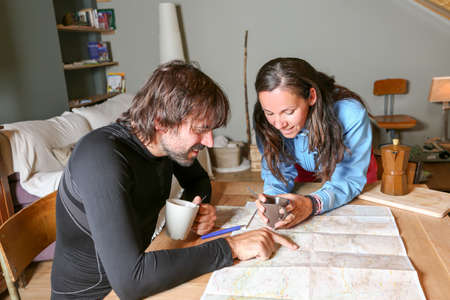 couple of mountaineers sitting having coffee planning the route looking at a map in a shelter - focus on a young woman photo
