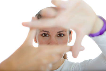 closeup of a young woman framing her eyes with hands isolated on a white background - focus on the eyes photo