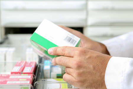 detail of the hands of a pharmacist taking a drug box from a drawer - focus on the left hand Standard-Bild