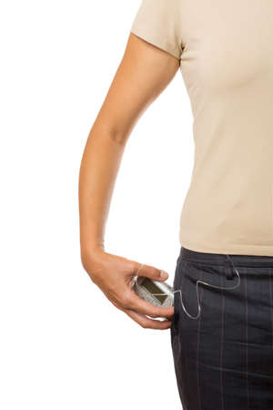 detail of a hand of a young woman standing keeping an insulin pump in her pocket Stock Photo