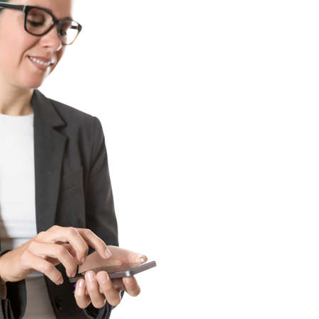 smiling business woman using a mobile phone isolated on a white background - focus on the hands and the mobile phone photo