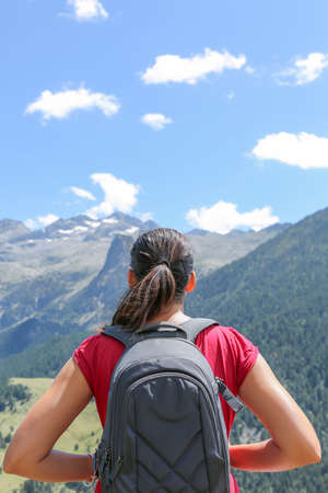 female hiker with backpack standing enjoying the view of the landscape on the top of the mountain Pyrinees Aragon Spain photo