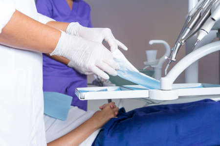 Nahaufnahme von den Händen eines weiblichen Zahnarzt Eröffnung einer Zahnmedizin-Start-Kit auf einem sterilisierten Beutel in einem Instrumentenhalter Tablett mit dem Behandlungsstuhl mit ihrer Assistentin und einem Patienten auf dem Hintergrund Standard-Bild