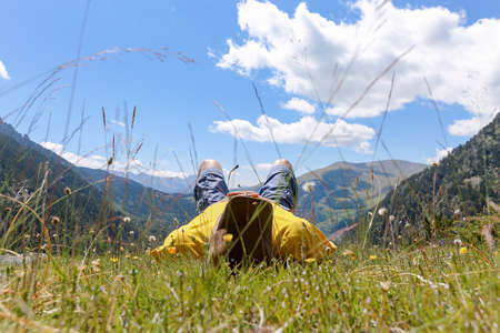 relaxed young man lying on a field of flowers enjoying the nature, the mountains and the blue sky - focus on the man photo