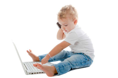 child sitting on the floor with phone and laptop isolated on a white background photo