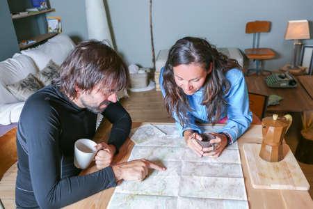 Paar Wanderer mit der Routenplanung sitzen um einen Tisch zeigt die Route auf einer Karte in einem gemütlichen Unterschlupf - Fokus auf die junge Frau