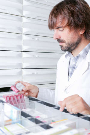 portrait of a young male pharmacist looking for a box of medicaments from a drawer - focus on the face photo