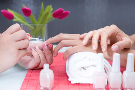 closeup of hands of a beautician painting the nails of a young woman with nail polish of the french manicure at the beauty salon - focus on the middle finger of the client Imagens