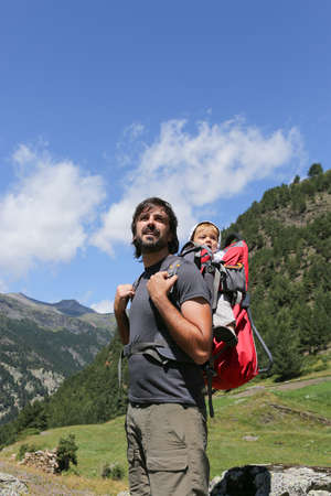 young male hiker carrying his baby in a backpack standing enjoying the beautiful view of the nature photo