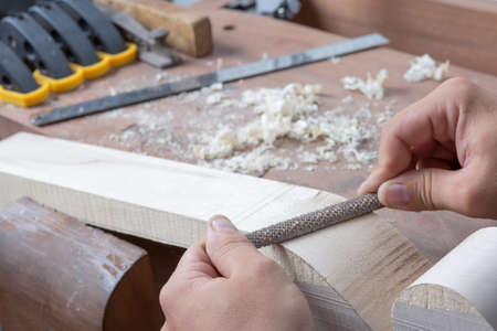 Detail der Hände eines Geigenbauers abgefeilt ein Cello Griff mit einem Metall Kalk in seiner Werkstatt - Fokus auf dem Kalk Standard-Bild