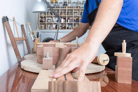 jungen männlichen Gitarrenbauer arbeitet in seiner Werkstatt in den Bau einer klassischen Gitarre über die Solera Standard-Bild