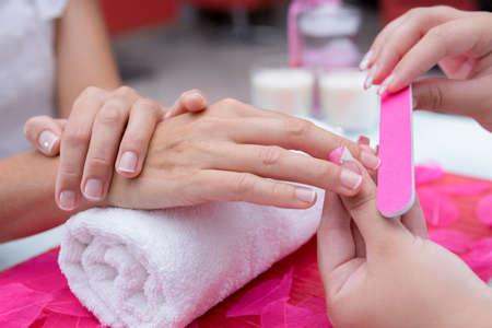 manicura: primer plano de las manos de una mujer joven que recibe la lima de u�as por una esteticista en el sal�n de belleza - se centran en el dedo medio Foto de archivo