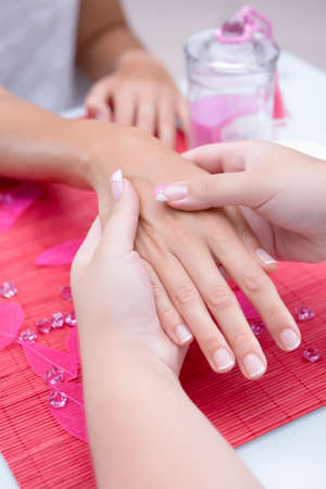 hands of a young woman receiving a hand massage by a beautician on a beauty session at the nail salon - focus on the right thumb photo