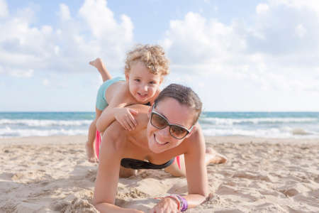 portrait of a happy mother and son playing together lying on the sand of the beach photo