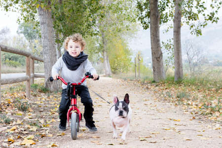 cute child walking his white and black french bulldog riding his bike by a path at the countryside Stock Photo
